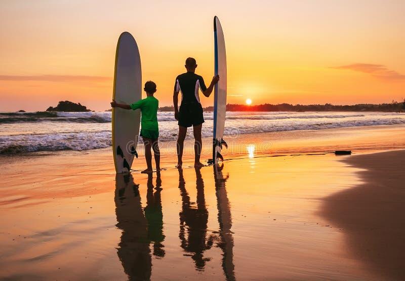 Vader en zoonssurfersverblijf op het zonsondergangstrand stock foto's