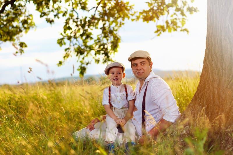 Vader en zoonszitting onder een oude eiken boom royalty-vrije stock fotografie