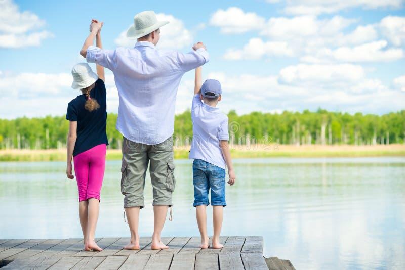 Vader gebrachte kinderen aan de rivier, die in openlucht kamperen stock foto's