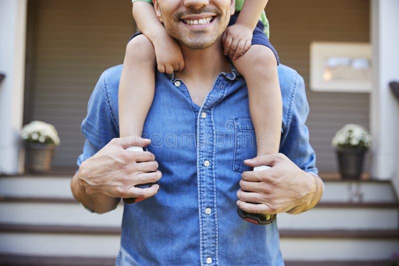 Vader Giving Son Ride op Schouders buiten Huis stock foto's