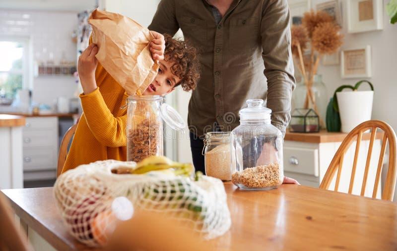 Vader helpt zoon om thuis voedselverpakkingen te hervullen met behulp van een verpakking zonder afval stock fotografie