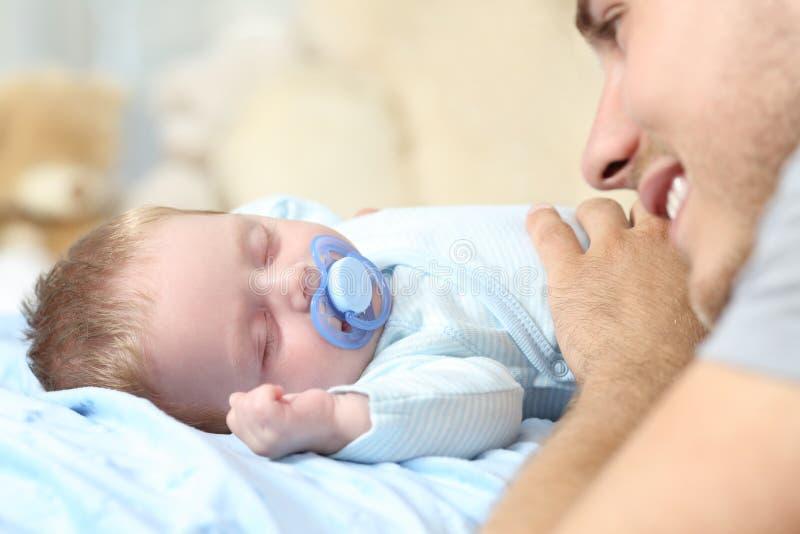 Vader het letten op aan haar babyslaap op bed royalty-vrije stock afbeelding