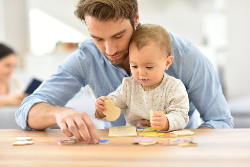 Vader het spelen met de raadsels van het babymeisje royalty-vrije stock afbeeldingen