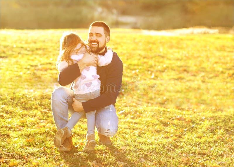 Vader het spelen met dochter in de herfstpark bij zonsondergang royalty-vrije stock fotografie