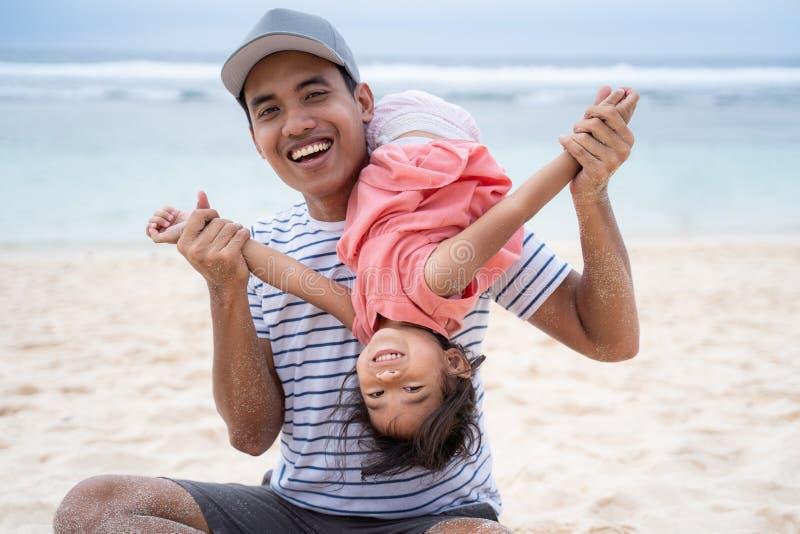 Vader het spelen met zijn dochtersalto mortale met de hoofd hieronder positie stock afbeeldingen