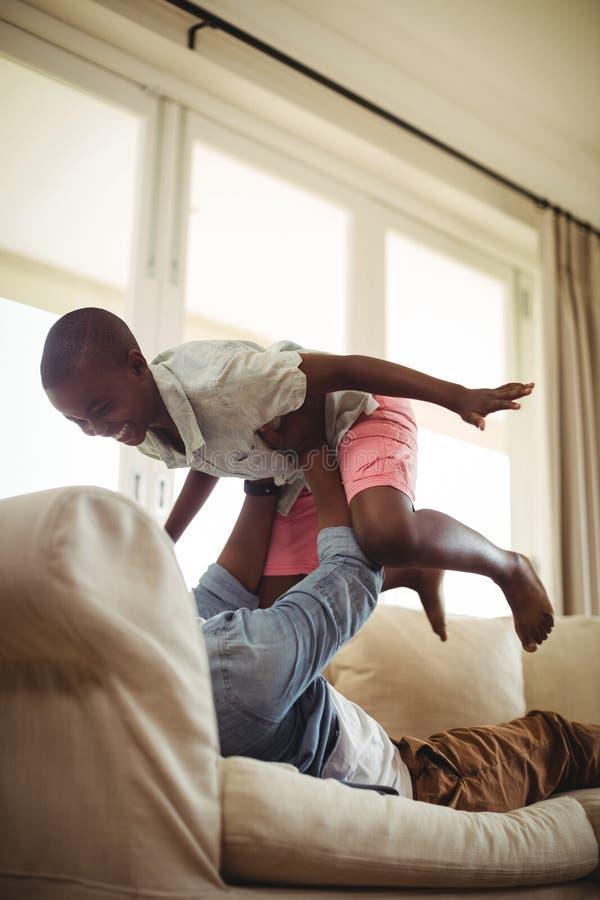 Vader het spelen met zoon op bank in woonkamer stock fotografie