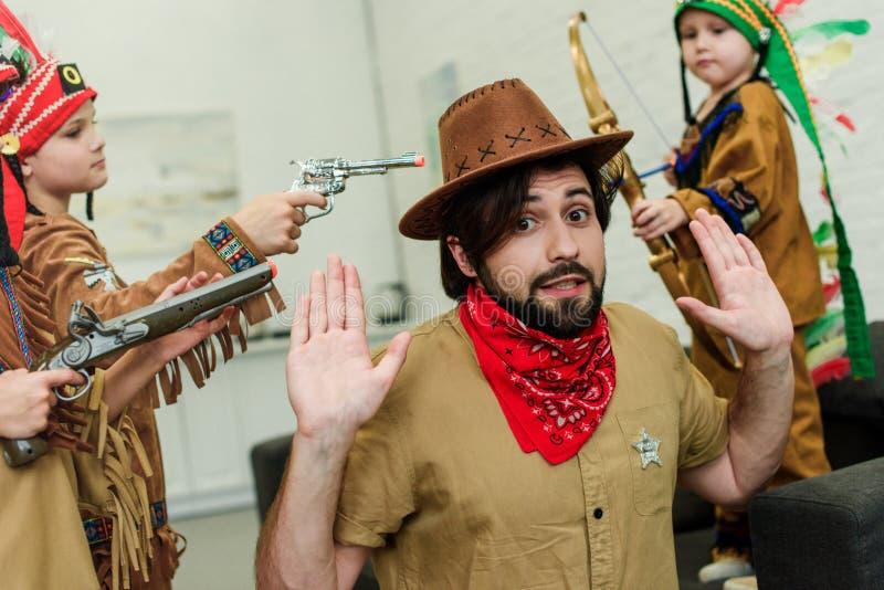 vader in hoed en bandana en kleine zonen die in inheemse kostuums met speelgoed samen spelen stock afbeelding