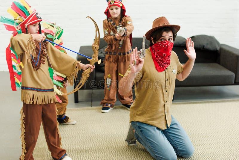 vader in hoed en bandana en kleine zonen die in inheemse kostuums met speelgoed samen spelen royalty-vrije stock afbeelding