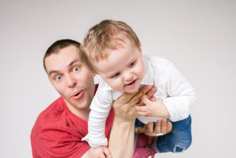 Vader met baby, die boven hoofd vliegen stock afbeeldingen
