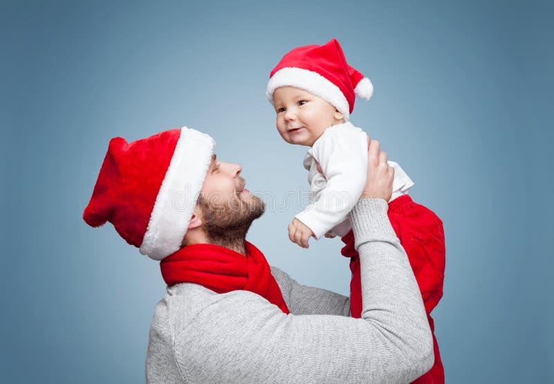Vader met babyjongen die Kerstmanhoeden dragen die Kerstmis vieren stock foto