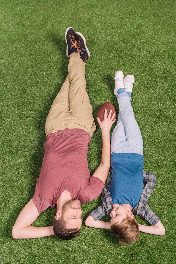 Vader met bal en weinig zoon die op het gras bij binnenplaats leggen royalty-vrije stock fotografie