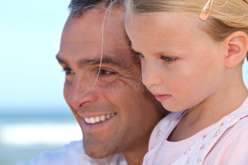 Vader met dochter door oceaan stock foto's