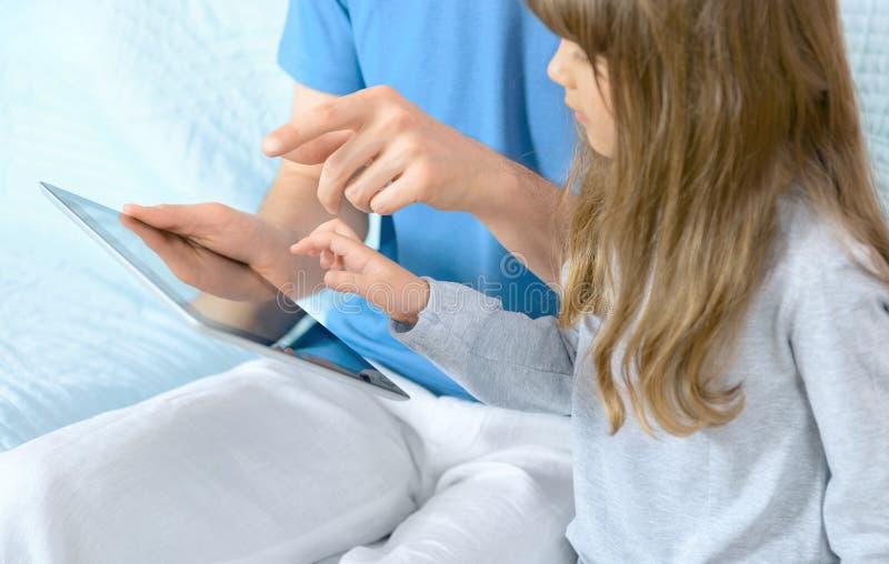 Vader met dochter het spelen op Appel Ipad stock afbeeldingen