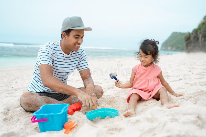 Vader met dochter het spelen zandkasteel stock foto's