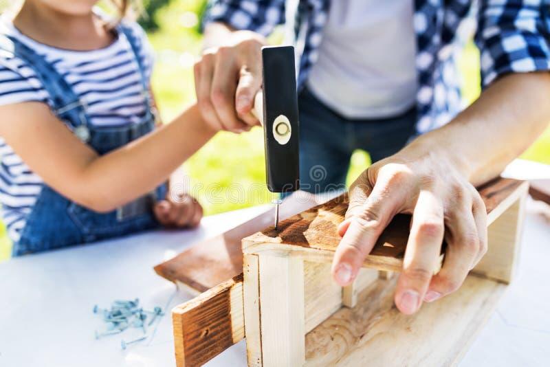 Vader met een kleine buiten dochter die, houten vogelhuis maken stock foto's