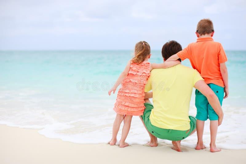 Vader met jonge geitjes bij strand stock afbeeldingen