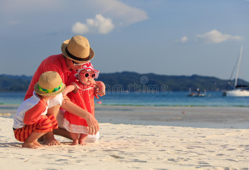 Vader met jonge geitjes die pret op het strand hebben stock fotografie