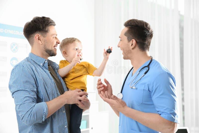 Vader met kind bezoekende arts stock foto's