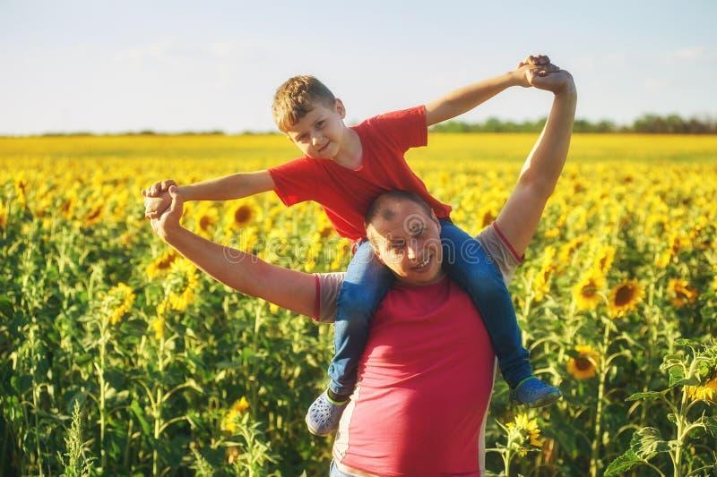 Vader met kind op een gebied van bloeiende zonnebloemen royalty-vrije stock fotografie
