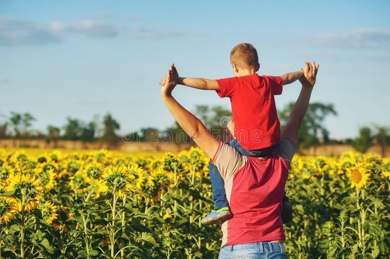 Vader met kind op een gebied van bloeiende zonnebloemen royalty-vrije stock foto