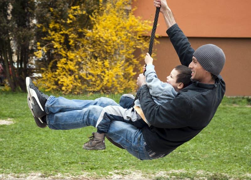 Vader met kind op schommeling royalty-vrije stock afbeelding