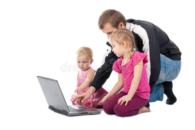 Vader met kinderen die op laptop spelen stock afbeelding
