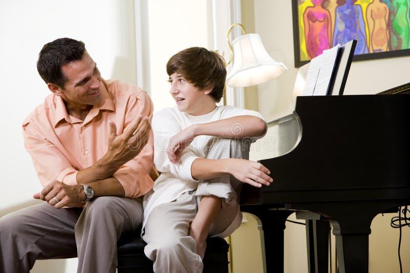 Vader met tienerzoon die thuis glimlacht stock foto's