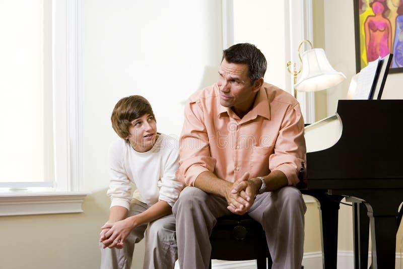 Vader met tienerzoonszitting samen thuis stock afbeeldingen
