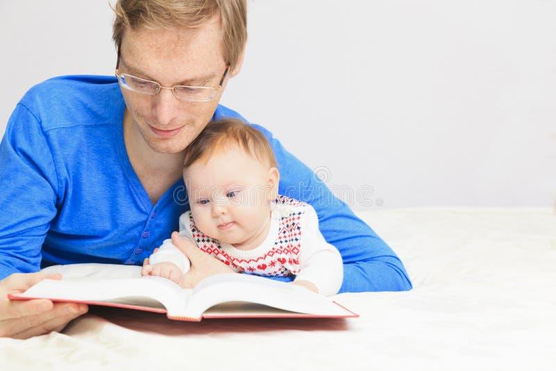 Vader met weinig dochterlezing thuis stock fotografie