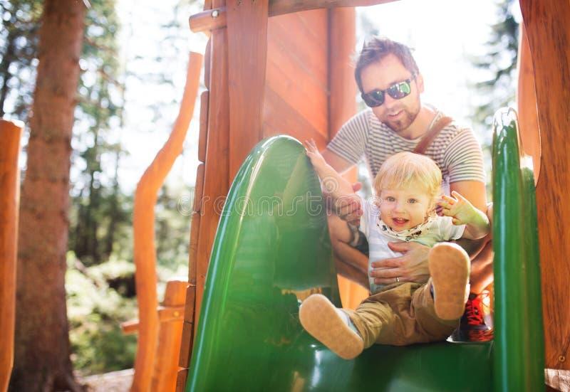 Vader met weinig jongen op de speelplaats royalty-vrije stock fotografie