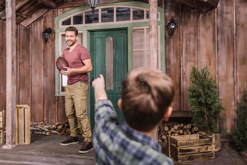 Vader met weinig zoon die Amerikaanse voetbal met bal spelen bij binnenplaats royalty-vrije stock afbeelding