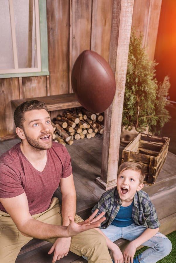 Vader met weinig zoon die Amerikaanse voetbal met bal spelen bij binnenplaats stock fotografie