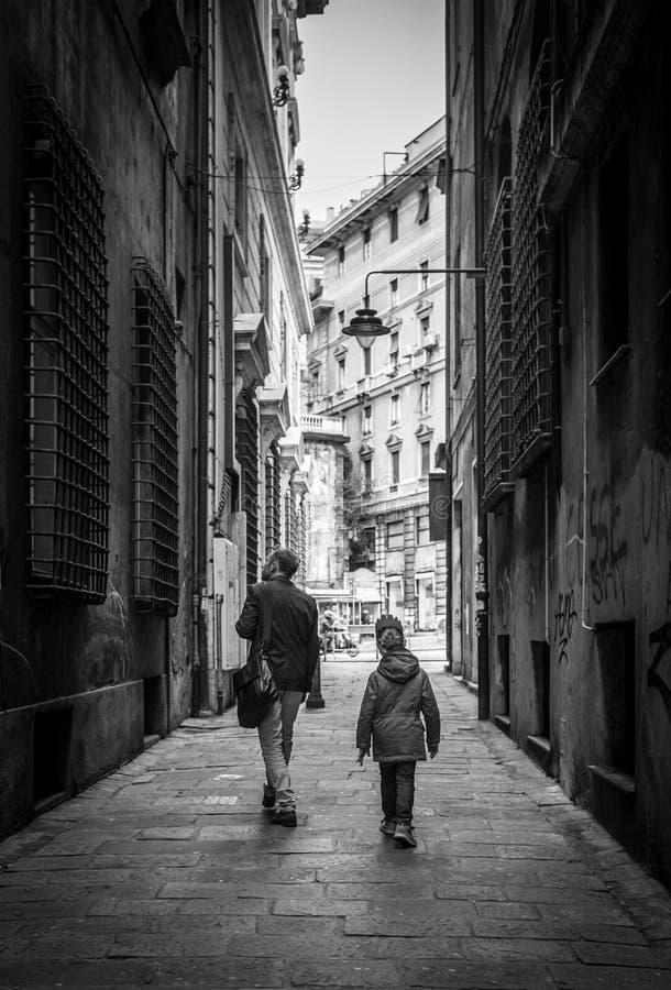 Vader met weinig zoon die door de smalle oude Italiaanse straten lopen stock foto