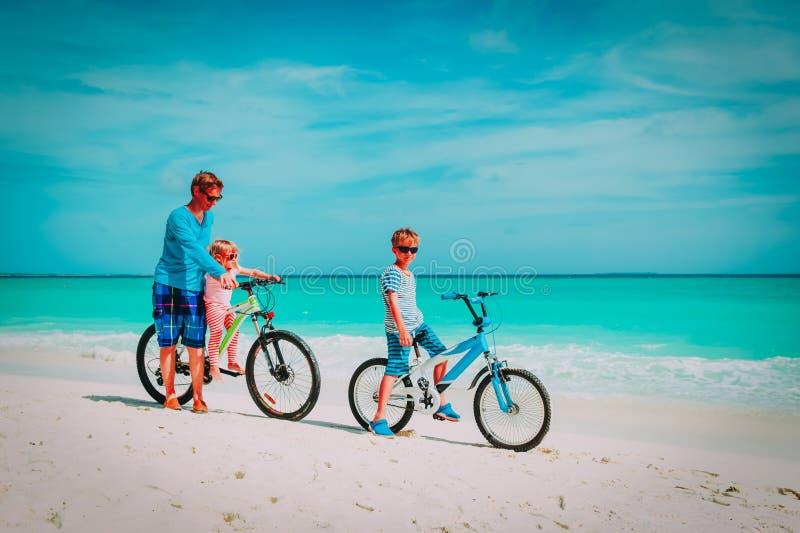 Vader met weinig zoon en dochter het biking op strand royalty-vrije stock afbeeldingen