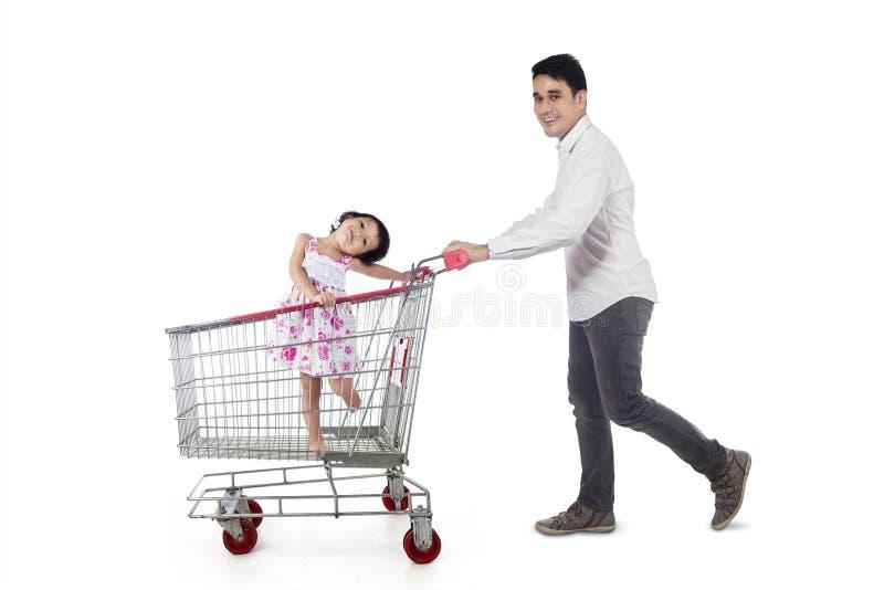 Vader met zijn dochter op karretje stock foto