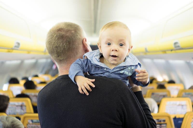 Vader met zijn zes van de babymaanden oud jongen in het vliegtuig stock foto's