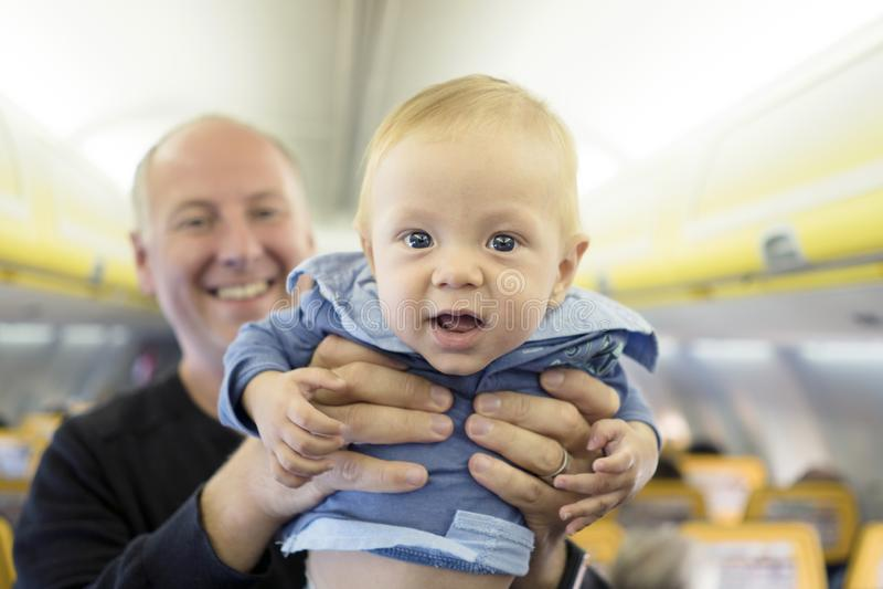 Vader met zijn zes van de babymaanden oud jongen in het vliegtuig stock afbeelding