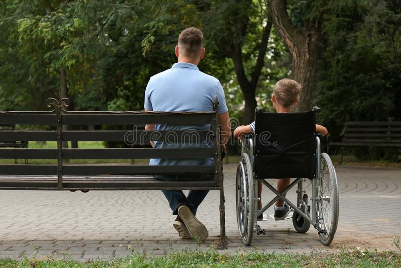 Vader met zijn zoon in rolstoel stock fotografie