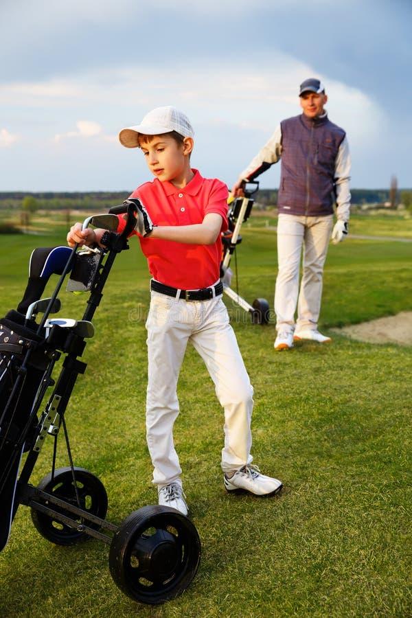 Vader met zoon bij golf royalty-vrije stock afbeelding