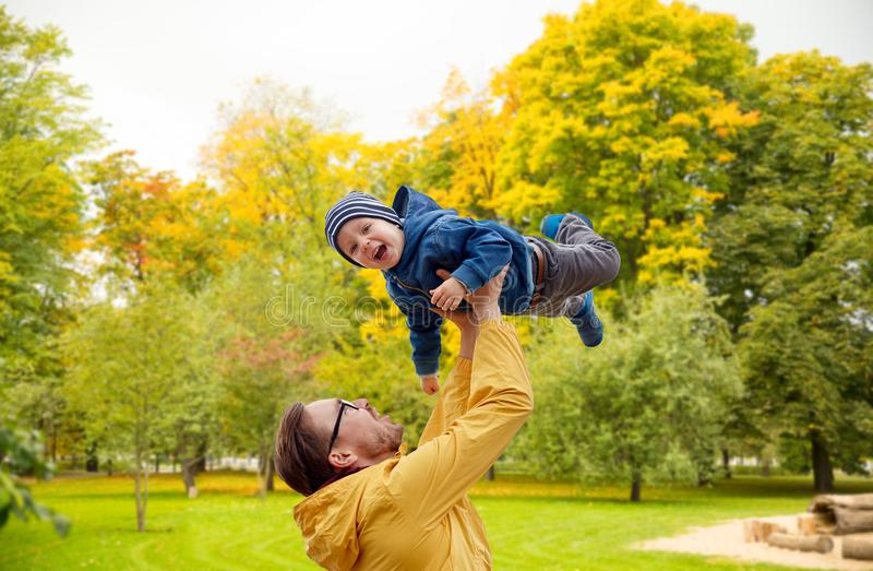 Vader met zoon die en pret in de herfst spelen hebben stock afbeeldingen