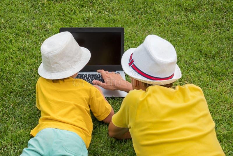 Vader met zoon het liggen op het gras dichtbij laptop Siblings en gadget openlucht Het besteden van de vader en van de zoon tijd  stock foto's