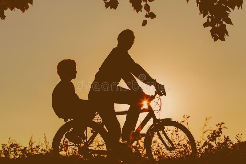 Vader met zoons berijdende fietsen bij zonsondergang royalty-vrije stock fotografie