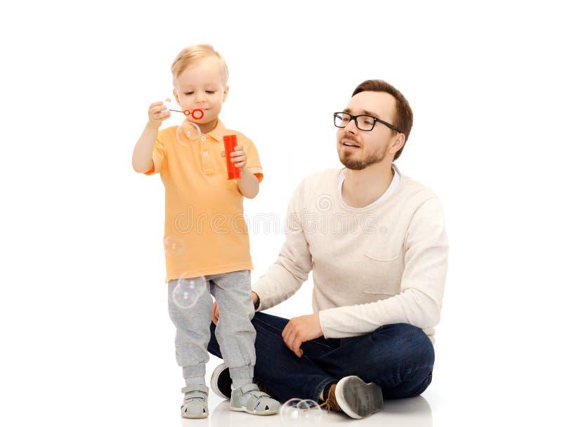 Vader met zoons blazende bellen en het hebben van pret royalty-vrije stock foto