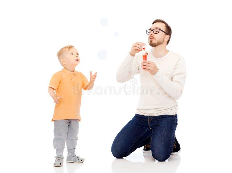 Vader met zoons blazende bellen en het hebben van pret stock afbeelding