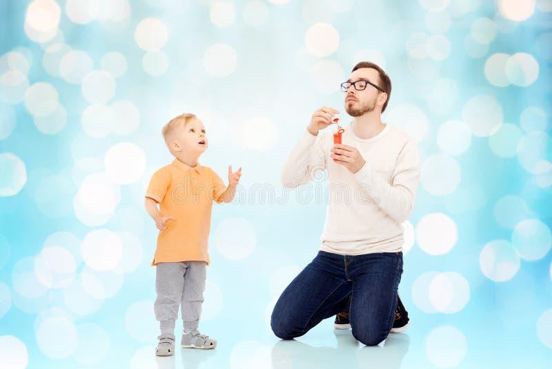 Vader met zoons blazende bellen en het hebben van pret stock foto