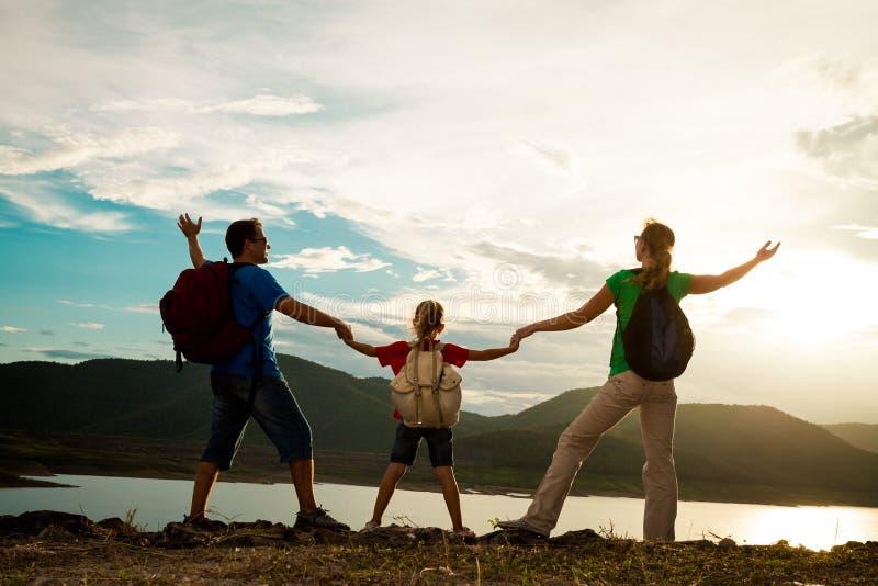 Vader, moeder en dochter die zich op de kust van meer bij bevinden stock fotografie