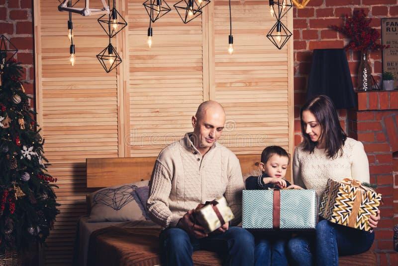 Vader, moeder en zoons de zitting op de laag en het bekijken hun Kerstmis stellen voor royalty-vrije stock foto