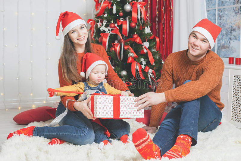 Vader, moeder en zuigelings de gift van holdingscristmas dichtbij Kerstboom stock foto's