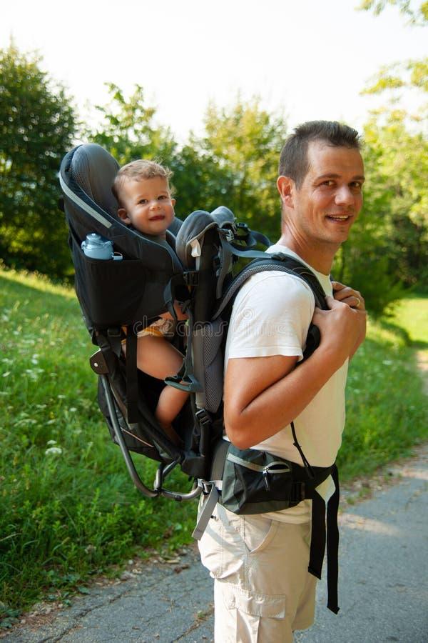 Vader op een gang met kik in de rugzak van de kinddrager stock foto's
