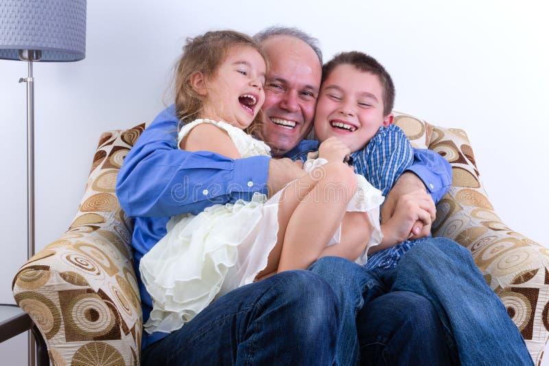 Vader op middelbare leeftijd met twee het lachen jonge geitjes stock foto's